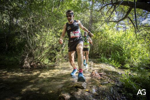 corredor de trail running cruzando el río albiol en Trail Albiol
